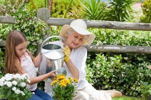 oma met haar kleindochter die in de tuin werkt foto