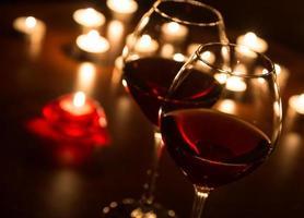 twee wijnglazen bij kaarslicht foto