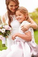 mooie bruid met bruidsmeisje buitenshuis foto