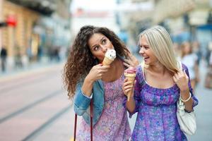 twee tienermeisjes die ijs in bloemenjurken eten foto