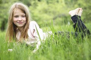 schattig klein meisje in het bos weide foto