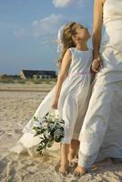 bruid en bloemenmeisje op strand foto