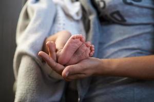 moeder houdt miniatuur pasgeboren voeten in handen foto