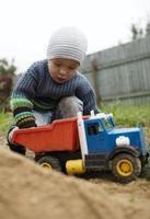 jongen speelt met speelgoed vrachtwagen buiten foto