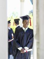 jonge man afstuderen in cap en jurk met diploma foto