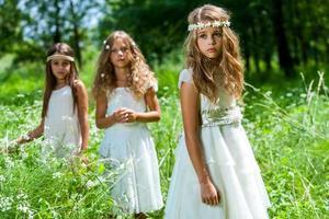 drie meisjes dragen witte jurken in het bos.