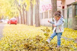 kind geniet van schoppen met bladeren foto