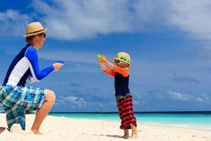vader en zoon spelen met waterkanonnen op het strand