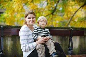 schattige kleine zoon en moeder in herfst stad.