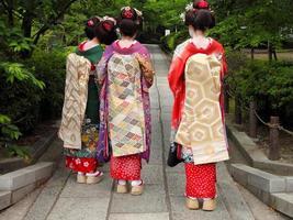 een achteraanzicht van drie geishameisjes foto