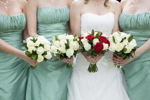 sluit omhoog van bruid en bruidsmeisjes die bloemen houden foto