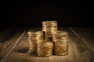 stapels gouden munten op een natuurlijke donkere achtergrond foto