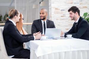 zakelijke bijeenkomst zakelijke partners. vier lachende succesvolle busi foto