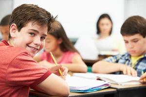 leerlingen studeren aan bureaus in de klas foto