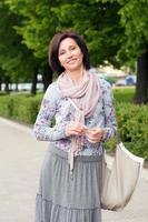 portret van lachende brunette vrouw in park foto