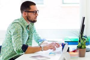 knappe zakenman werken met laptop op kantoor. foto