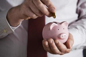 zakenman munt aanbrengend spaarvarken foto