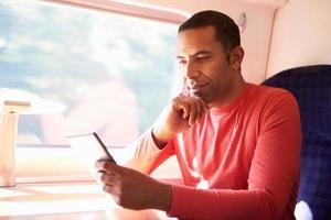 man leest een elektronisch boek op een trein