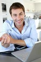 gelukkig thuiswerker met behulp van laptop en smartphone foto