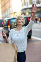 toevallige vrouw die een taxicabine begroet foto