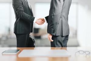 twee zakenlieden schudden elkaar de hand in het kantoor foto