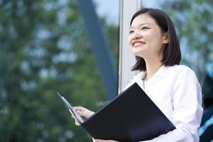 jonge Aziatische vrouwelijke uitvoerende bedrijf bestand in de zakenwijk foto