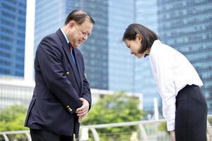 Aziatische zakenman en jonge vrouwelijke uitvoerende buigen voor elkaar foto