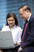 Aziatische zakenman en jonge vrouwelijke executive met behulp van laptop pc foto