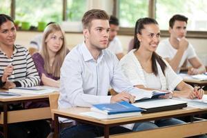 mannelijke student die een lezing in klaslokaal luistert foto