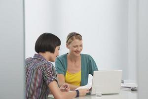 glimlachende vrouwen die laptop in bureau met behulp van foto
