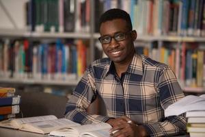 Afrikaanse man studeren in een bibliotheek foto