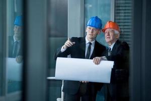 jonge ingenieur praten met senior baas foto