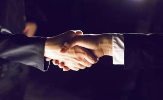handshake handshaking op licht en donker foto
