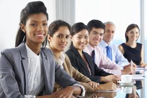 lijn van mensen uit het bedrijfsleven luisteren naar presentatie zittend op glas foto