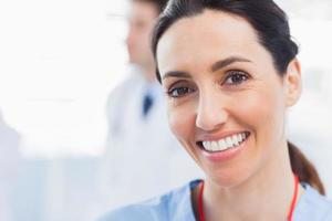 glimlachende verpleegster die camera met een arts achter haar bekijkt foto