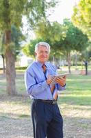 zakenman die en een tablet werkt houdt foto