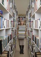 oudere vrouw met boeken in bibliotheek