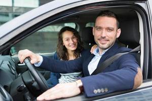 jonge zakenman paar in hun gloednieuwe auto foto