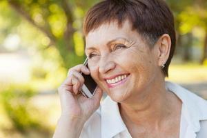 mooie vrouw van 50 jaar met een mobiele telefoon buitenshuis foto