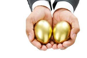 close-up van zakelijke hand met gouden eieren foto