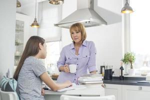 moeder die koffie heeft terwijl het bekijken dochter het bestuderen in keuken foto