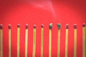 verbrande match setting op rode achtergrond voor ideeën en inspiratie foto