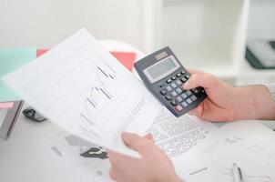 zakenman handen met rekenmachine foto