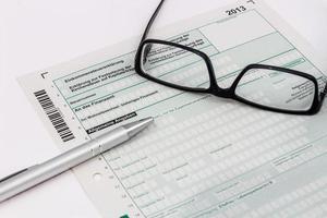 vorm van aangifte inkomstenbelasting met balpen en bril