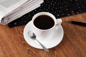 zakelijk stilleven met kop zwarte koffie foto