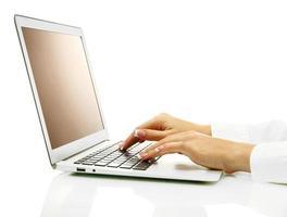 vrouwelijke handen die op laptot schrijven, die op wit wordt geïsoleerd foto