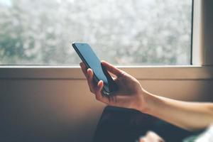 man met zijn smartphone sluit het raam foto