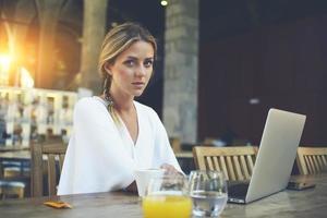 mooie vrouwelijke freelancer die netboek gebruikt voor afstandswerk in een café foto