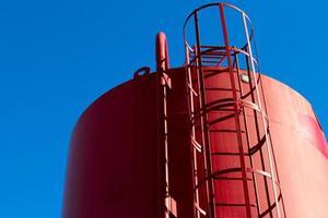rode vuilwatertank met ladder en blauwe hemel foto