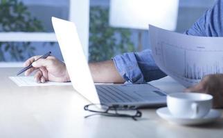 man aan het werk thuis op laptopcomputer foto